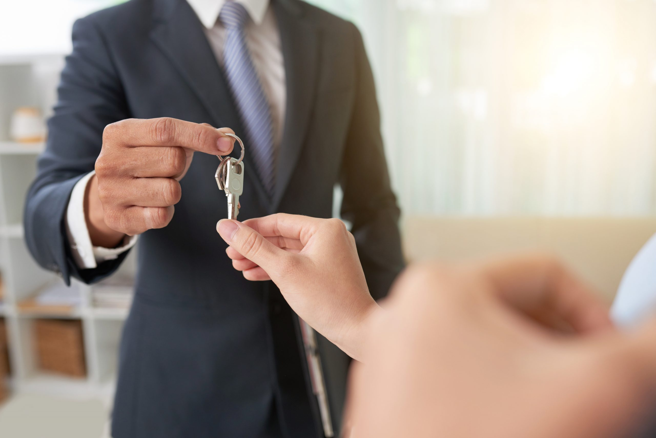 Hand of woman taking keys from hand of real estate owner