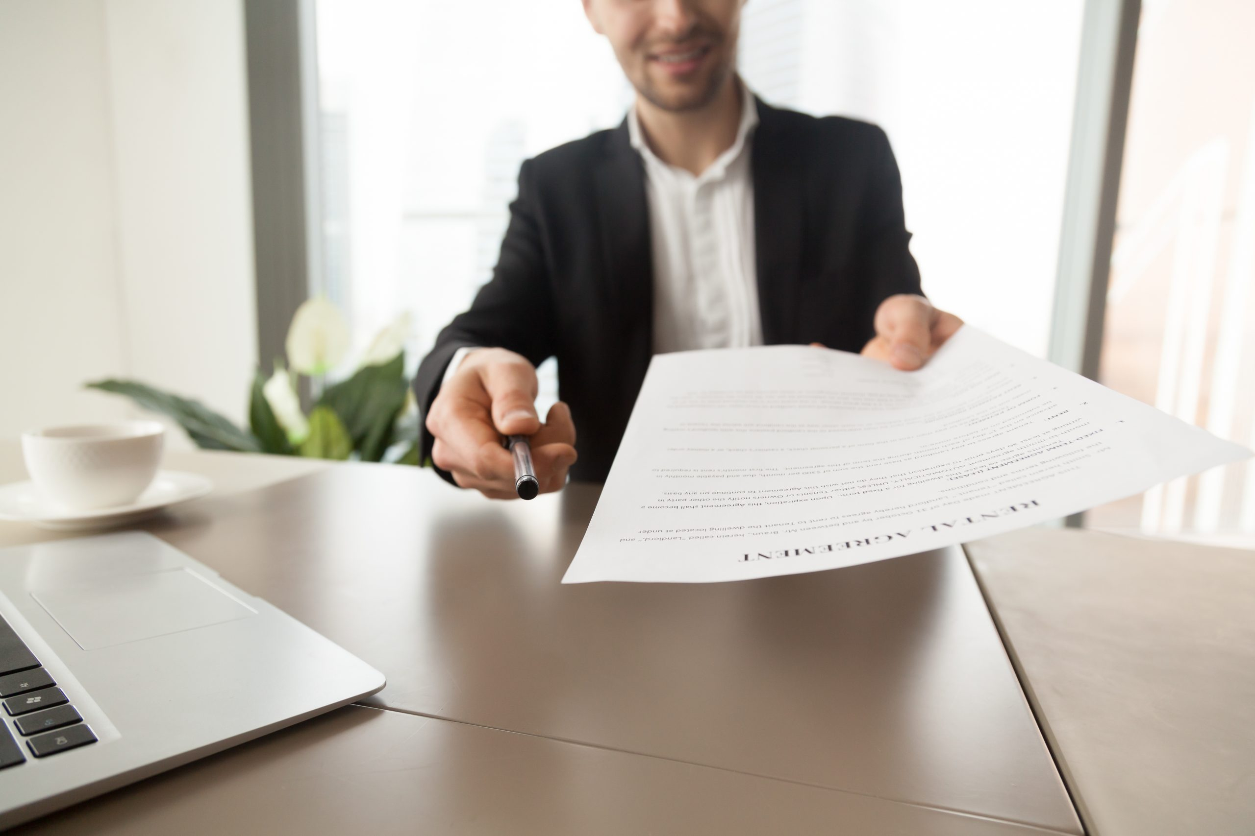 Realtor reaching out pen and rental agreement to clients. Real estate consultant sitting at desk in office and offers to read and sign contract document. Readiness to make a deal, rent new dwelling